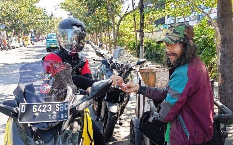 Anggota komunitas Bebas Bermotor Bersama (Bebeb Bikers) membagikan uang kepada masyarakat di jalan. (Foto: Bebeb Bikers & MB W211 CI)