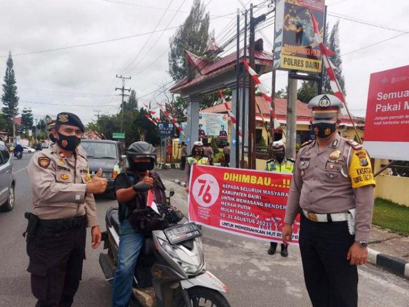 Polres Dairi membagi-bagikan bendera Merah Putih kepada para pengendara di jalan raya (Foto: Instagram Polres Dairi)